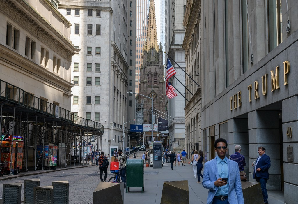 People walk near the New York Stock Exchange (NYSE) at Wall Street. AFP Photo