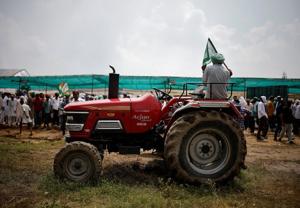 A farmer sits on a tractor as he attends a Maha Panchayat or grand village council meeting as part of a protest against farm laws in Muzaffarnagar. Reuters