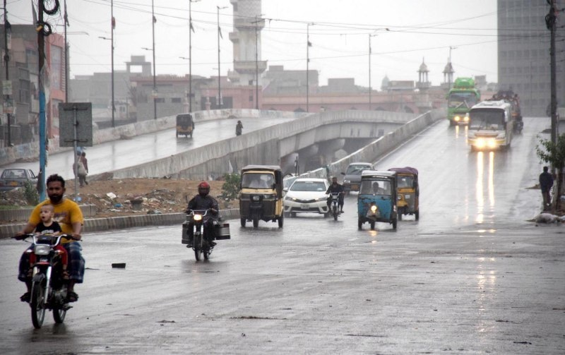 Pic05-040 KARACHI: July05-People are on their way on MS Rafique Road during light rain as weather become pleasant after rain. ONLINE PHOTO by Syed Asif Ali
