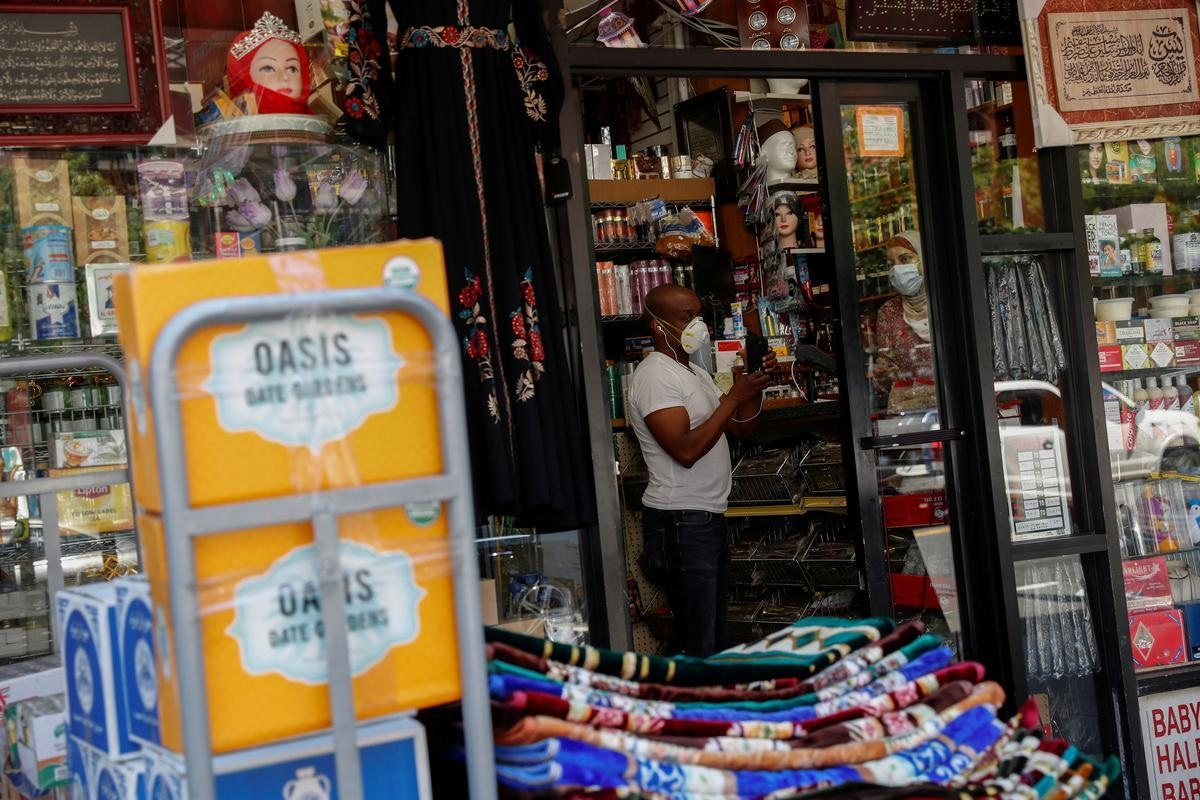 FILE PHOTO: A shopkeeper works inside his retail store as the phase one reopening of New York City continues during the outbreak of the coronavirus disease (COVID-19) in the Brooklyn borough of New York City, New York, U.S. June 9, 2020. REUTERS