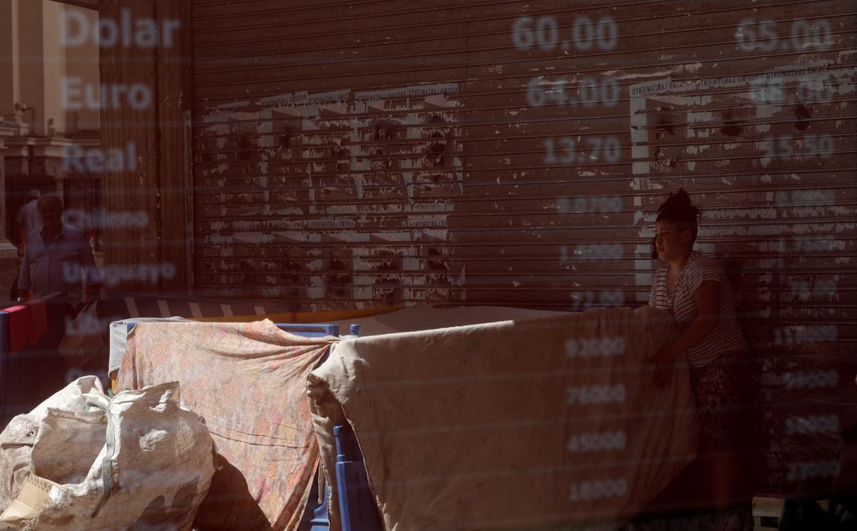 FILE PHOTO: A homeless woman is reflected in an electronic board showing currency exchange rates, in Buenos Aires, Argentina December 11, 2019. REUTERS