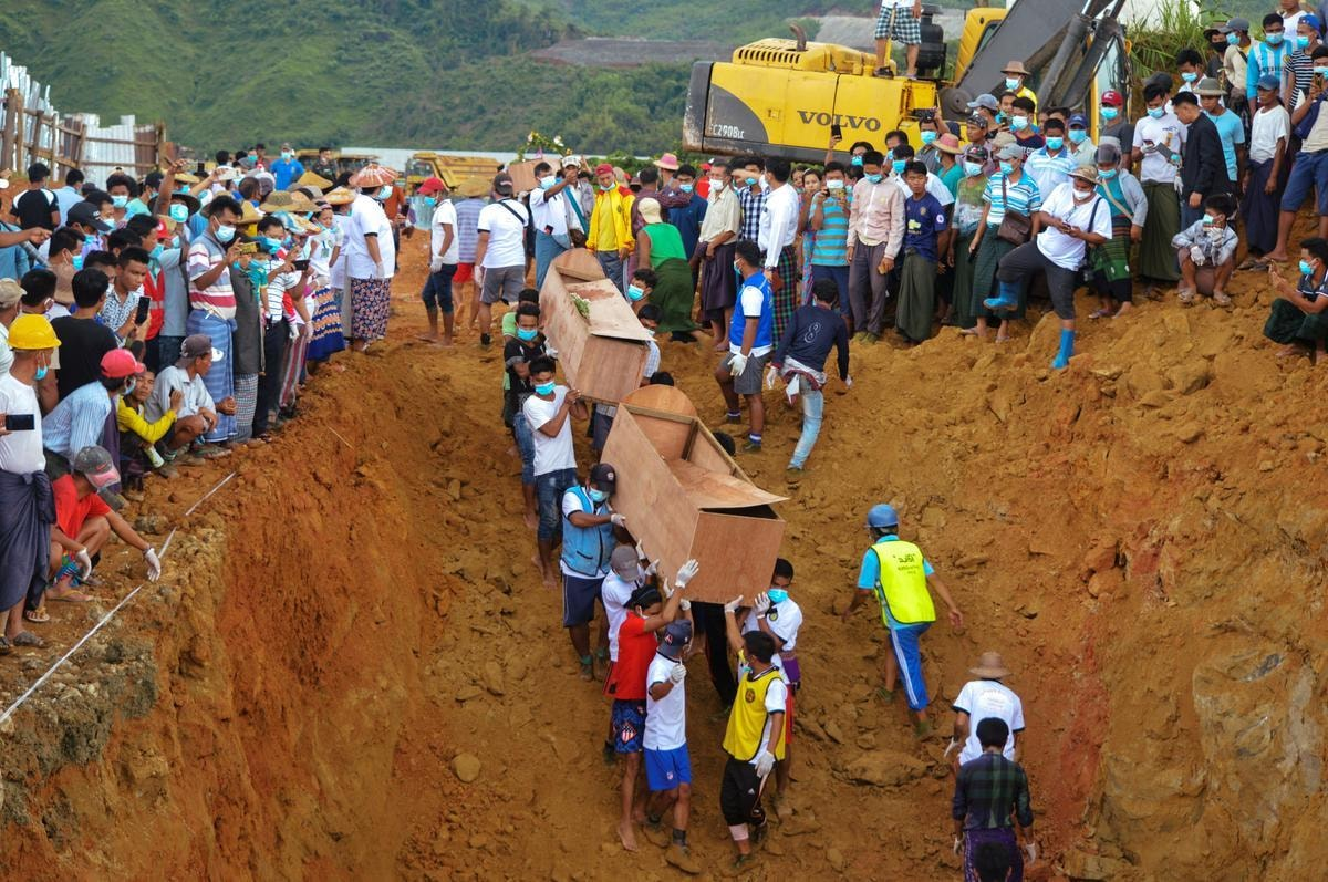 FILE PHOTO: Volunteers carry coffins containing bodies of victims following a landslide at a mining site in Hpakant, Kachin State City, Myanmar July 3, 2020. REUTERS