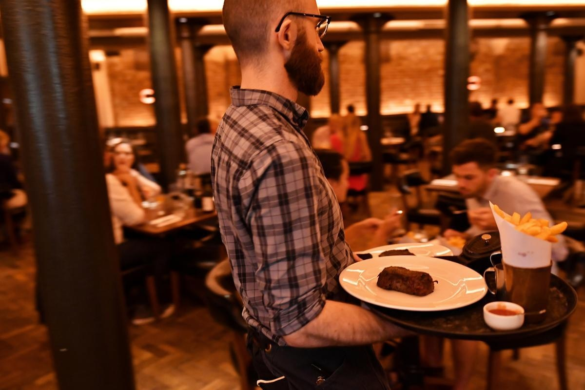 """Staff work at Hawksmoor, Seven Dials on the opening day of """"Eat Out to Help Out"""" scheme, amid the coronavirus disease (COVID-19) pandemic, in London, Britain August 3, 2020. Picture taken August 3, 2020. REUTERS"""