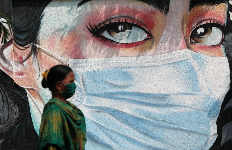 A woman walks past a graffiti of a girl wearing a protective mask amidst the spread of the coronavirus disease (COVID-19) in Mumbai, India, October 23, 2020. REUTERS