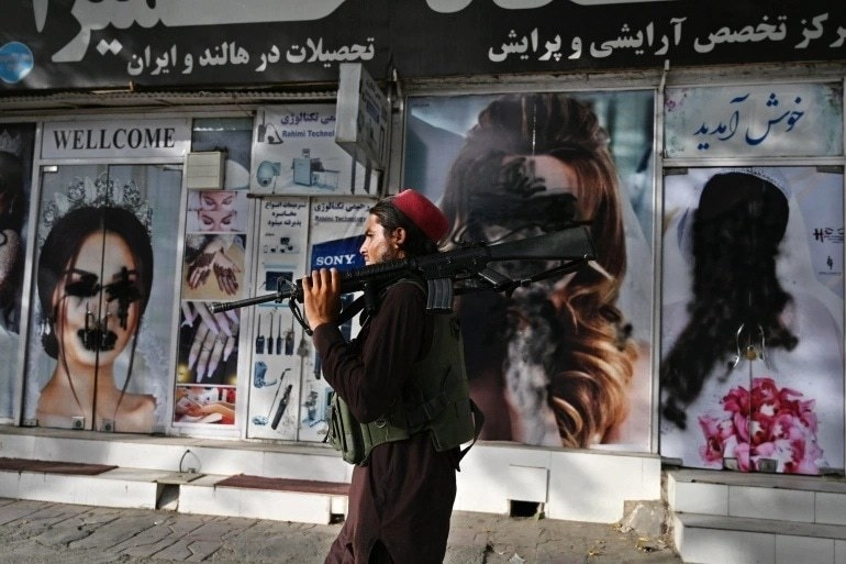 A Taliban fighter walks past a beauty salon with images of women defaced using spray paint in Shar-e-Naw in Kabul on August 18, 2021. — AFP