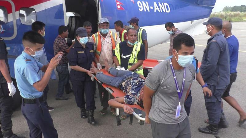 One among many passengers injured in a bus accident in western Nepal's Mugu district is rushed for treatment after being airlifted to Nepalgunj, Nepal, Tuesday, Oct.12, 2021. AP Photo