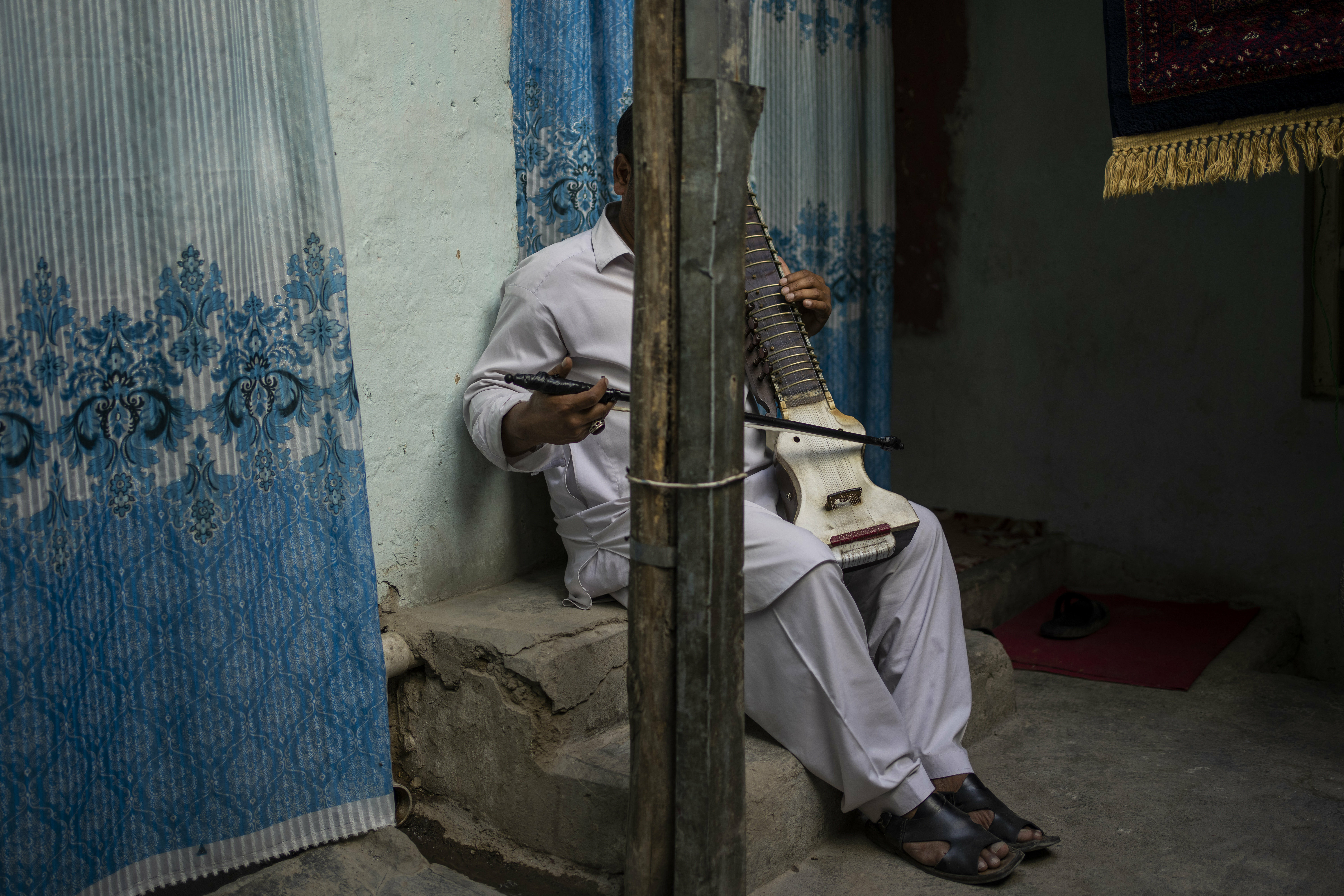 An Afghan musician poses for a portrait with his dilruba in Kabul, Afghanistan, Saturday, Sept. 18, 2021. About a month after the Taliban seized power in Afghanistan, the music is starting to go quiet. The last time that the militant group ruled the country, in the late 1990s, it outright banned music. (AP Photo/Bernat Armangue) — Copyright 2021 The Associated Press. All rights reserved